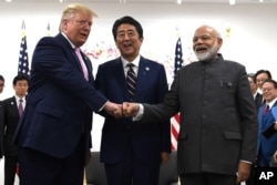 President Donald Trump, Japanese Prime Minister Shinzo Abe and Indian Prime Minister Narendra Modi share a fist bump during their meeting on the sidelines of the G-20 summit in Osaka, Japan, June 28, 2019.