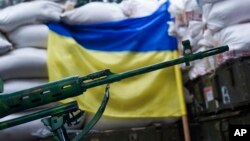 A rifle is seen in front of a Ukrainian flag in the village of Mariinka, near Donetsk, eastern Ukraine, Aug. 25, 2016.