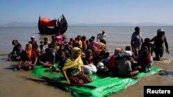 Rohingya refugees sit on a makeshift boat as they await permission from Border Guard Bangladesh to continue after crossing the Bangladesh-Myanmar border, at Shah Porir Dwip near Cox's Bazar, Bangladesh, Nov. 9, 2017.