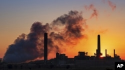 FILE - In this July 27, 2018, file photo, the Dave Johnson coal-fired power plant is silhouetted against the morning sun in Glenrock, Wyo.