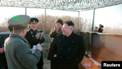 North Korean leader Kim Jong Un and officials observe the test firing of a new type of anti-ship cruise missile in this undated photo released by North Korea's Korean Central News Agency in Pyongyang, Feb. 7, 2015.