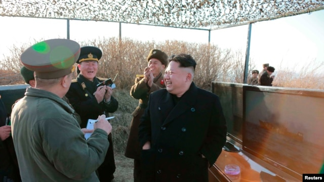 FILE - North Korean leader Kim Jong Un and officials gather for the test firing of a new type of anti-ship cruise missile in this undated photo released by North Korea's Korean Central News Agency in Pyongyang, Feb. 7, 2015.