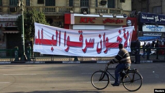 Một người đàn ông Ai Cập đạp xe qua biểu ngữ với hàng chữ 'Huynh đệ Hồi giáo đã ăn cắp đất nước' tại Quảng trường Tahrir ở Cairo, ngày 29/11/2012.