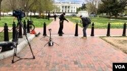 由于疫情关系,电视台记者们改到白宫外进行录影工作(美国之音黄耀毅)
