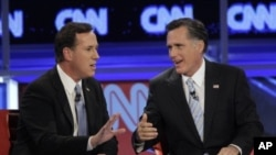 Republican presidential candidates, former Massachusetts Gov. Mitt Romney, right, and former Pennsylvania Sen. Rick Santorum argue a point during a Republican presidential debate, Mesa, Arizona, February 22, 2012.