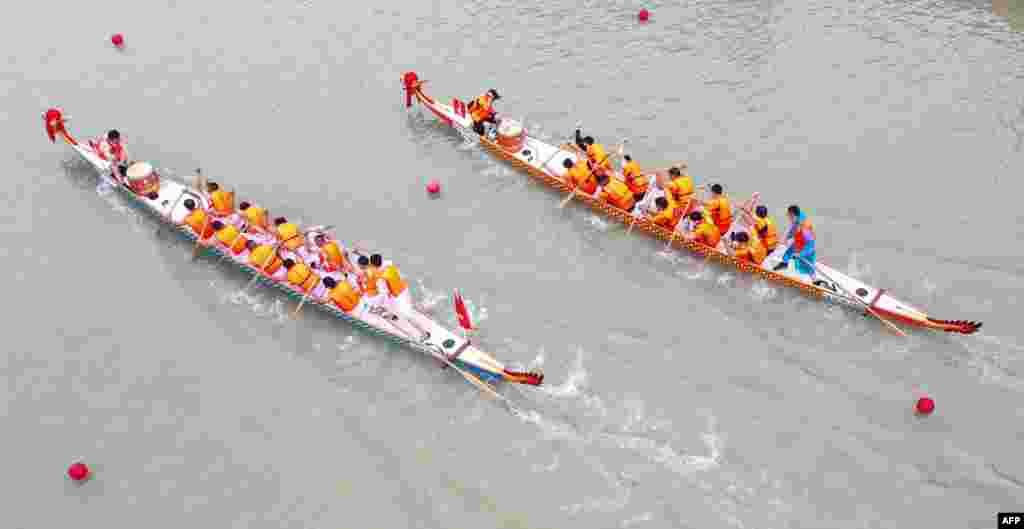 This aerial photo shows teams competing during a dragon boat race ahead of the Dragon Boat Festival in Huaian, in China's eastern Jiangsu province.