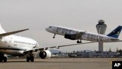 Phi trường Seattle, Hoa Kỳ. Một máy bay cất cánh theo chỉ dẫn từ tháp không lưu, một chiếc đang chờ trên đường băng