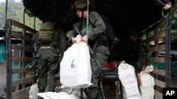 FILE - A counter narcotics police officer loads bags containing cocaine seized in Chinacota, near Colombia's northeastern border with Venezuela, March 2, 2016.
