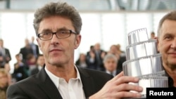 "Polish director Pawel Pawlikowski poses with his trophy after he was awarded the Lux cinema prize of the European Parliament for his film ""Ida' during a ceremony at the European Parliament in Strasbourg, France, Dec. 17, 2014."