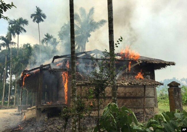 FILE - Flames engulf a house in Gawdu Zara village, northern Rakhine state, Myanmar, Sept. 7, 2017. In a video, widely circulated in Myanmar, a respected Buddhist monk blamed arson incidents in Rakhine state on Muslim extremists.