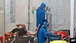 បុគ្គលិកសុខាភិបាលព្យាបាលអ្នកជំងឺកូវីដ១៩ នៅក្នុងតង់សម្រាប់ការសង្គ្រោះបន្ទាន់មួយ នៅមន្ទីរពេទ្យ Dr. Sardjito General Hospital ក្នុងទីក្រុង Yogyakarta ប្រទេសឥណ្ឌូណេស៊ីកាលពីថ្ងៃទី៤ ខែកក្កដា ឆ្នាំ២០២១។