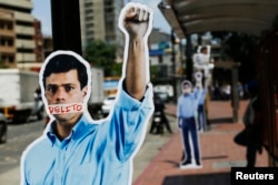 Cardboard figures of jailed opposition leader Leopoldo Lopez with his mouth covered with the word 'Crime' are seen during a gathering in support of him in Caracas June 4, 2014.