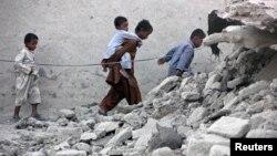 25일 파키스탄 아와란 지역에서 지진이 일어난 가운데 아이들이 무너진 집 사이로 걷고 있다.