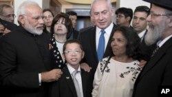 نریندر مودی (بائیں) اور اسرائیلی وزیر اعظم بنجمن نتن یاہو(درمیان) ایک اسرائیلی لڑکے موشے ہولٹزبرگ سے مل رہے ہیں جس کے والدین نومبر 2008 کے ممبی حملے میں ہلاک ہو گئے تھے۔ 5 جولائی 2017