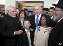 Indian Prime Minister Narendra Modi, left, with Israeli Prime Minister Benjamin Netanyahu, center right, meet with with Moshe Holtzberg, center, an Israeli boy whose parents were killed in the Nov. 26, 2008 terrorist attack on Mumbai.