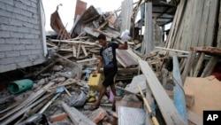 Seorang pria berusaha menyelamatkan barang-barangnya di antara reruntuhan Senin (18/4), sementara isterinya yang hamil dilaporkan tewas akibat gempa di La Chorrera, Ekuador hari Sabtu.