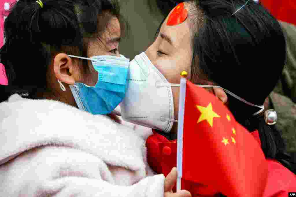 A medical staff member kisses her daughter after returning home from Wuhan helping with the COVID-19 coronavirus recovery effort, in Bozhou, in China's eastern Anhui province.