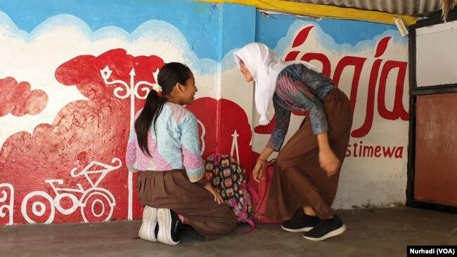 Dua siswi kelas 6 SDN Bangunrejo 2 mengambil tas yang sebelumnya mereka letakkan di poskamling, Jumat (7-2). (Foto: VOA/ Nurhadi)