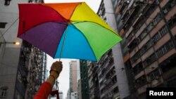 Seorang peserta memakai payung pelangi saat mengikuti parade LGBT di Hong Kong (foto: dok).