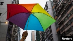 A participant holds a rainbow umbrella as he attends a lesbian, gay, bisexual and transgender (LGBT) Pride Parade in Hong Kong, Nov. 8, 2014. Participants from the LGBT communities took to the streets to demonstrate for their rights.