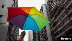 2014年一名同性恋骄傲大游行的参与者手举一把彩虹伞。众多参与者走上街头要求平权。