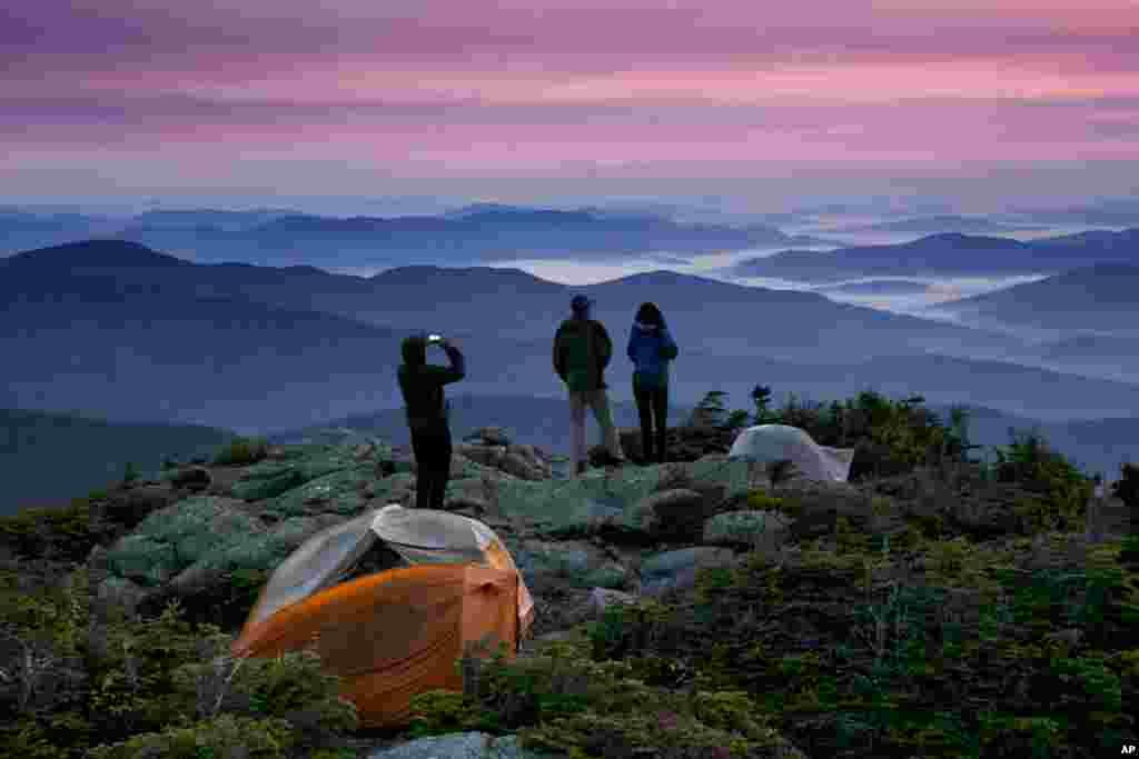 Para pendaki menikmati suasana matahari terbit dari kawasan pegunungan Beans Purchase, negara bagian New Hamphire, AS.