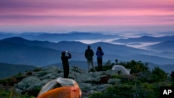 Robert Weiss of Tewksbury, Mass., left, photographs his brother-in-law, Matthew Ferri, of Dracut, Mass., and his wife, Andrea Weiss just before sunrise from their campsite on the Appalachian Trail in Beans Purchase, N.H., Sunday, Sept. 17, 2017. (AP Photo/Robert F. Bukaty)