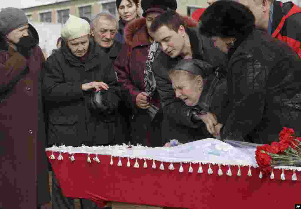 The mother of a miner killed in an explosion on Wednesday at more than 1,000 meters (3,200 feet) underground at the Zasyadko mine, is supported by relatives during a funeral for the victims of the accident in Donetsk, Ukraine.  At least 33 miners have been confirmed dead.