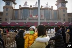 2020年1月21日北京站外抱着戴口罩孩子的一名妇女