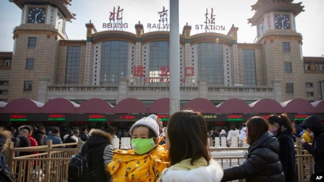 Las autoridades chinas no dan abasto a la demanda de máscaras para protegerse del nuevo brote de un coronavirus en la ciudad de Wuhan. Esta foto muestra a una madre con su hija en Beijing.