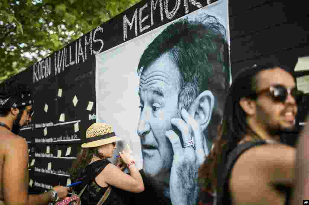 Festival goers pay tribute to the late actor Robin Williams at a makeshift memorial at the 22nd Sziget (Island) Festival on the Shipyard Island in northern Budapest, Hungary, Aug. 13, 2014.