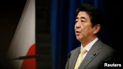 FILE - Japan's Prime Minister Shinzo Abe speaks next to the Japanese national flag.