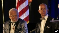 Apollo 11 astronaut Buzz Aldrin, left, and Amazon.com and Blue Origins founder Jeff Bezos attend the commemoration for the upcoming anniversary of the 1969 mission to the moon and a gala for Aldrin's nonprofit space education foundation, ShareSpaceFoundation, at the Kennedy Space Center in Cape Canaveral, Fla., July 15, 2017.