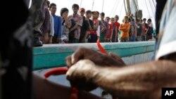 Petugas di Indonesia memberi pita di pergelangan tangan nelayan Burma yang telah diselamatkan sebagai identifikasi saat tiba di Tual (4/4). (AP/Dita Alangkara)