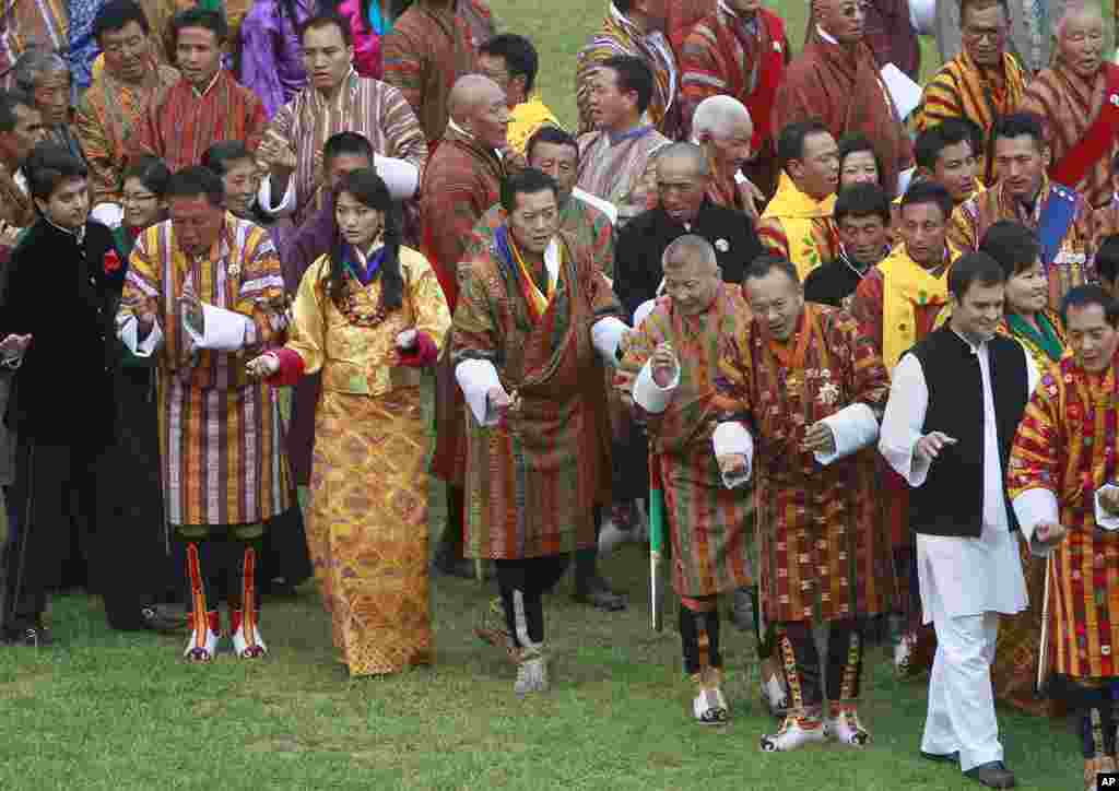 Bhutan's King Jigme Khesar Namgyel Wangchuck, center, and Queen Jetsun Pema, center left, perform the traditional final dance with guests at the main stadium, including Indian Member of Parliament Rahul Gandhi, bottom second right, as part of their weddi