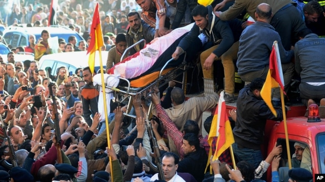Egyptians carry the coffin of a victim killed from an explosion at a police headquarters, during the funeral procession of a dozen policeman and a civilian killed, in the Nile Delta city of Mansoura, north of Cairo, Egypt, Dec. 24, 2013.