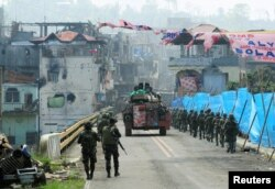 An armored personnel carrier and government troops march toward Mapandi bridge after 100 days of intense fighting between soldiers and insurgents from the Maute group, who have taken over parts of Marawi city, southern Philippines, Aug. 30, 2017.