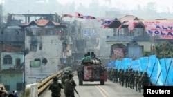 Sebuah kendaraan lapis baja (APC) dan pasukan pemerintah berbaris menuju jembatan Mapandi setelah berlangsungnya pertempuran sengit antara tentara dan pemberontak dari kelompok Maute selama 100 hari, yang telah mengambil alih bagian kota Marawi, Filipina selatan 30 Agustus 2017.