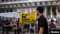 """Người biểu tình ủng hộ dân chủ ngồi nghỉ dưới biểu ngữ với hàng chữ """"Chúng tôi không phải là kẻ thù"""" bên ngoài một chi nhánh ngân hàng HSBC tại khu mua sắm Mongkok của Hồng Kông, ngày 7/10/2014."""