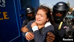A protester is detained during an attempt to deliver a petition, near the French embassy, in Phnom Penh January 21, 2014. Eleven protesters, including Cambodian activists Yorm Bopha and Tep Vanny, were detained while trying to deliver petitions to foreign embassies in Phnom Penh, calling for help in securing the release of 23 men who were jailed for joining a strike earlier this month over garment factory wages, according to local rights groups.