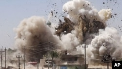 In this undated photo posted on a militant website that frequently carries official statements from the Islamic State extremist group, smoke and debris go up in the air as Shiite's Al-Qubba Husseiniya mosque explodes in Mosul.