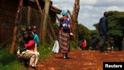 Seorang ibu menggendong anaknya di punggungnya di wilayah kumuh Kangemi, Nairobi, Kenya, 23 April 2013 (Foto: dok).