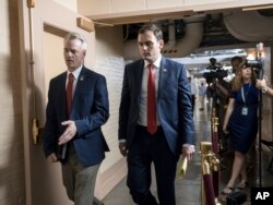 Rep. Steve Russell, R-Okla., left, and Rep. Mike Gallagher, R-Wis., walk to a closed-door meeting with House Republicans seeking more information about compromise legislation on immigration, at the Capitol in Washington, June 21, 2018.