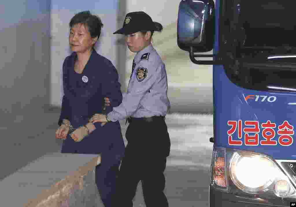 한국의 박근혜 전 대통령(왼쪽)이 서울 중앙지법 속행재판에 출석하기 위해 호송차에서 내려 법정으로 향하고 있다. 박 전 대통령의 변호인단은 추가 구속영장을 발부한 법원의 결정에 항의하며 전원 사임계를 제출했다.