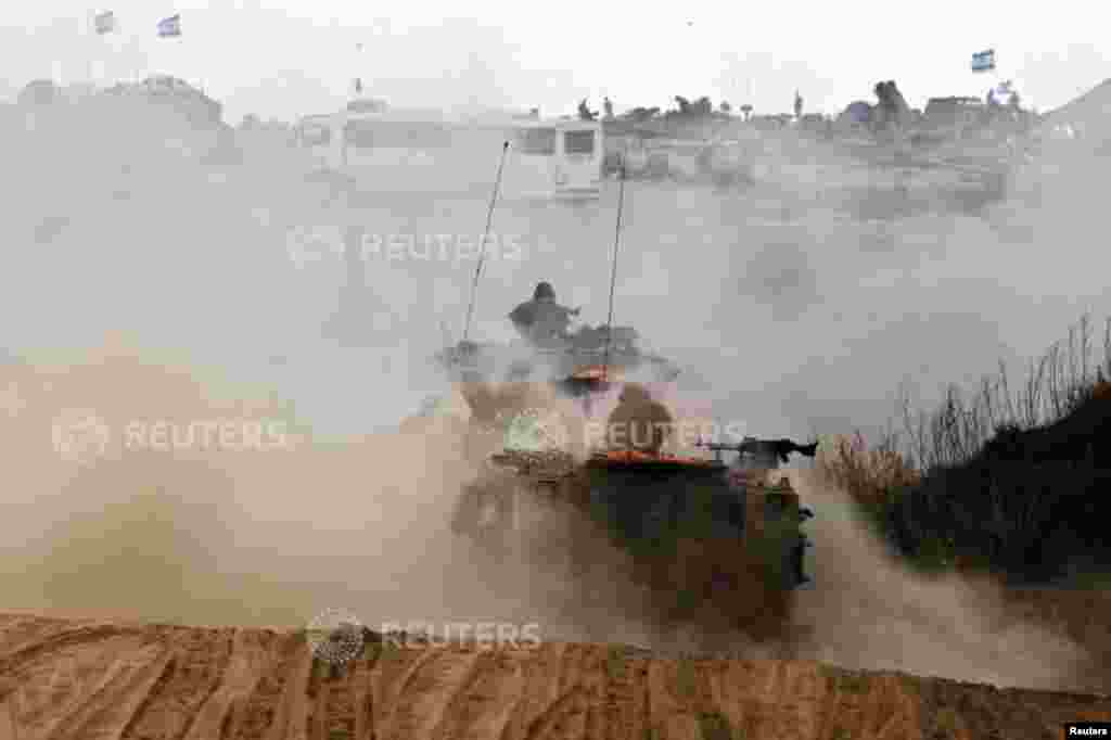 Israeli soldiers travel in armored personnel carriers, near the Gaza Strip, July 15, 2014.