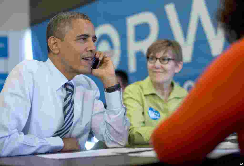 President Barack Obama calls to thank volunteers in Wisconsin, at campaign office call center the morning of the 2012 election, Tuesday, Nov. 6, 2012, in Chicago. Carla Windhorst is seated next to the president. (AP Photo/Carolyn Kaster)