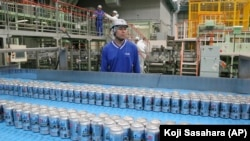 In this Monday, May 29, 2017 photo, Asahi Breweries plant manager Shinichi Uno watches the production line at an Asahi Breweries factory in Moriya near Tokyo. The human job is to make sure the machines do the work right, and to check on the quality