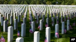 FILE - Flags placed in front of every headstone at Arlington National Cemetery in Arlington, Va.