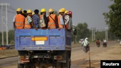 Workers are transported via truck to the site of the Thilawa Special Economic Zone (SEZ) project at Thilawa May 8, 2015. REUTERS/Soe Zeya Tun/File Photo - S1BEUBGAUIAA