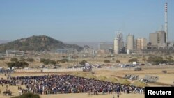 Mineworkers queue for check-ins near Lonmin's Marikana platinum mine before returning to work, June 25, 2014.